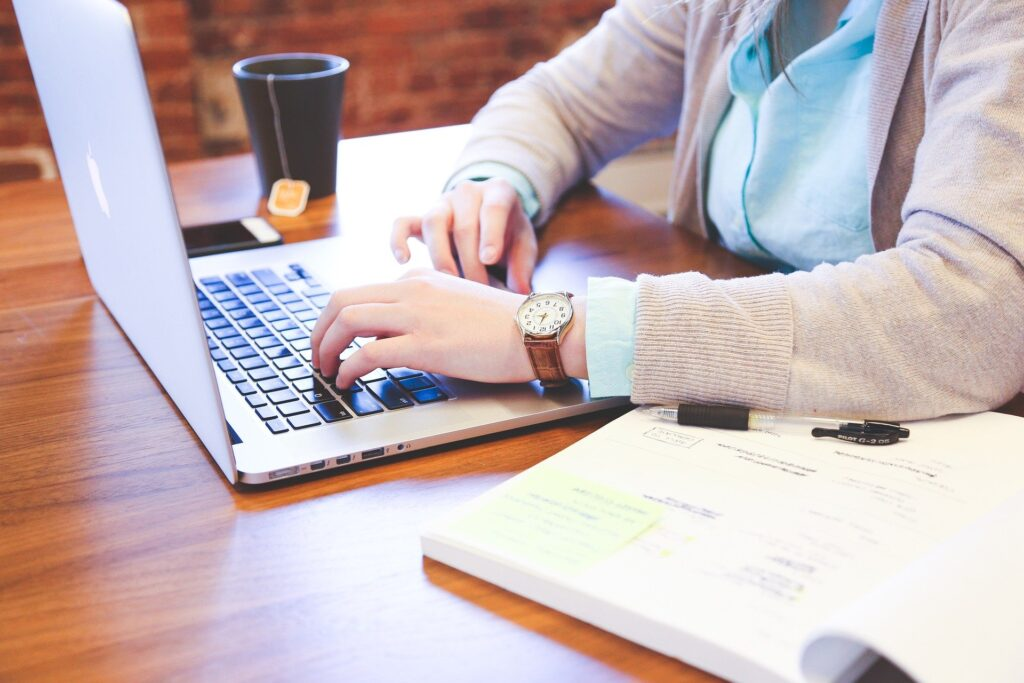 picture of a woman's hands on a laptop with a cup of tea nearby